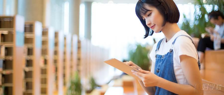 摄图网_500557533_wx_坐在图书馆使用平板的女生(企业商用)