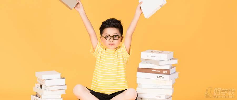 摄图网_500925934_wx_拿着书本坐在书旁的快乐男孩(企业商用)